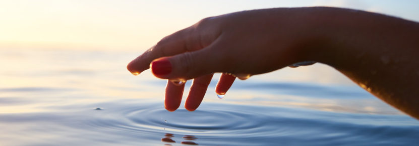 Hand touching water, creating ripples.